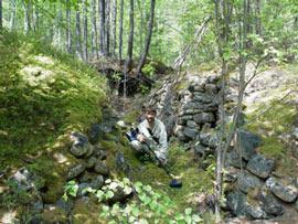 Надпойменную террасу разрезала траншея в рост человека поросшая молодыми деревцами и прочей растительностью.